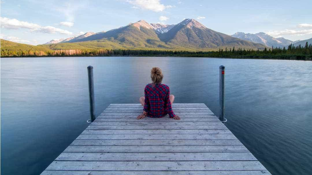 Image of a woman sitting on a pier looking at mountains